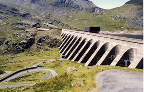 The upper reservoir and dam of the Ffestiniog Pumped-Storage Scheme in north Wales.The power station at the lower reservoir has four water turbines which can generate 360 megawatts of electricity within 60 seconds of the need arising. The water of the upper reservoir (Llyn Stylan) can just be glimpsed on the right.